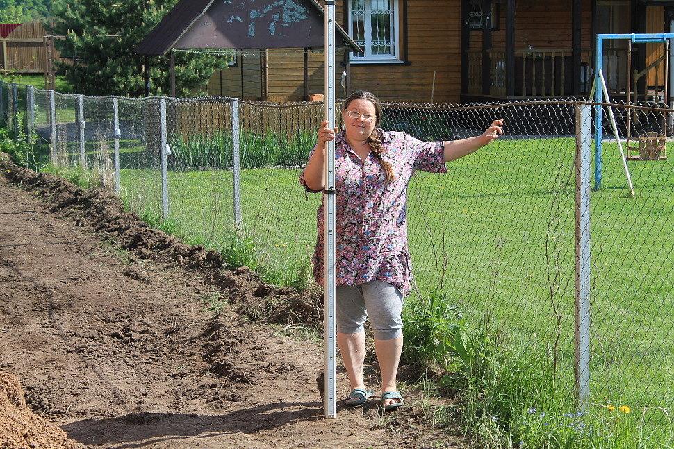 Татьяна с рейкой в руках помогает с замерами высот